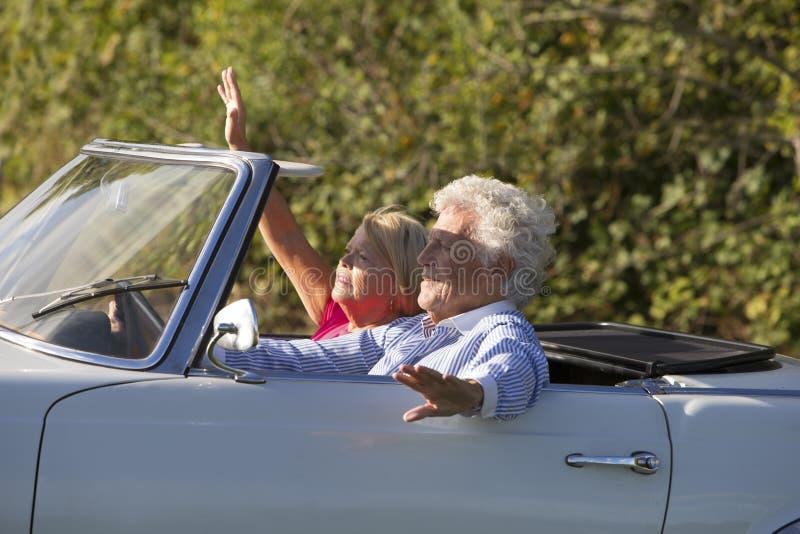 Pares superiores felizes no carro de esportes do vintage fotografia de stock