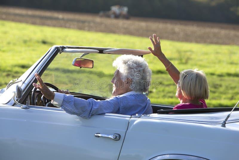 Pares superiores felizes no carro de esportes do vintage foto de stock