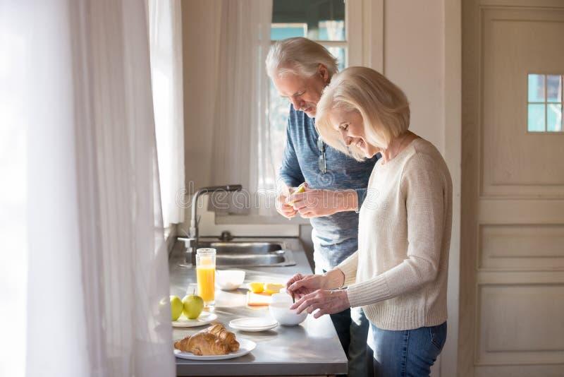 Pares superiores felizes para fazer o café da manhã saudável na cozinha da casa imagens de stock