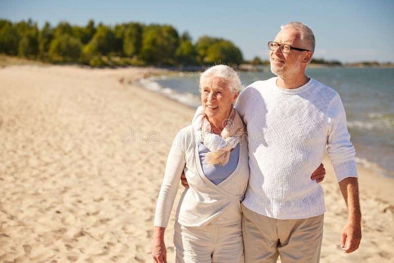 Pares superiores felizes que andam ao longo da praia do verão foto de stock royalty free