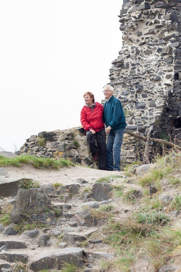 Pares superiores felizes que caminham no terreno rochoso fotografia de stock