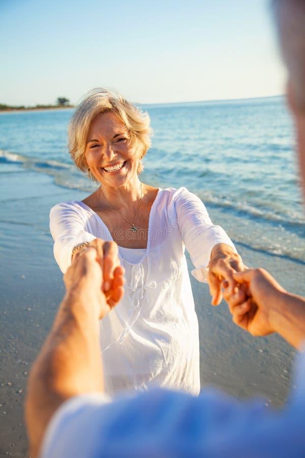 Pares superiores felizes que dançam guardando as mãos na praia do por do sol imagens de stock royalty free