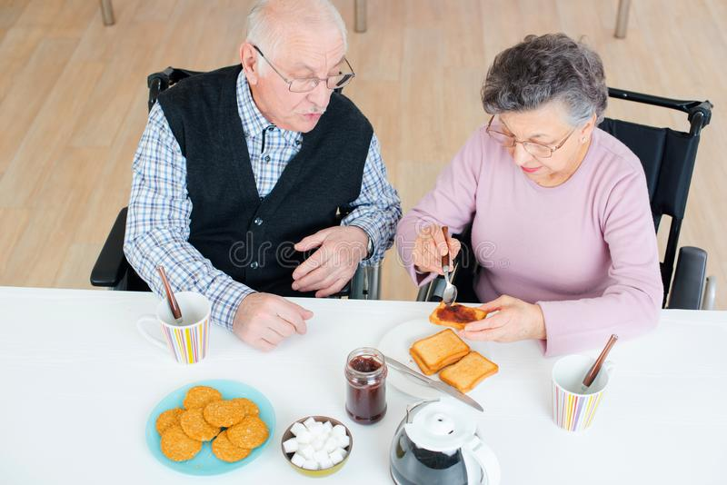 Pares superiores felizes que discutem ao comer o café da manhã na tabela fotografia de stock