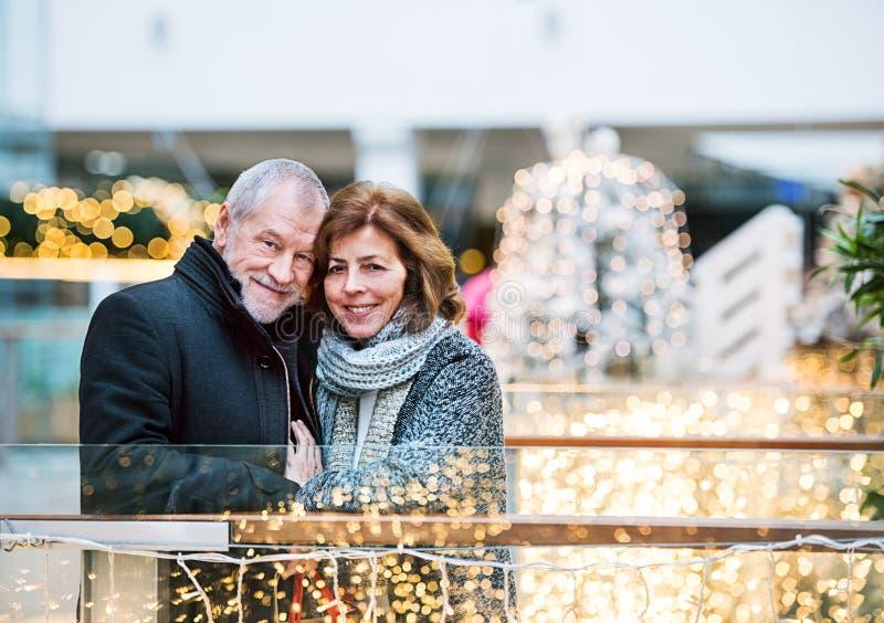 Pares superiores felizes que fazem o Natal que compra junto imagem de stock