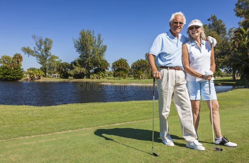 Pares superiores felizes que jogam o golfe foto de stock royalty free