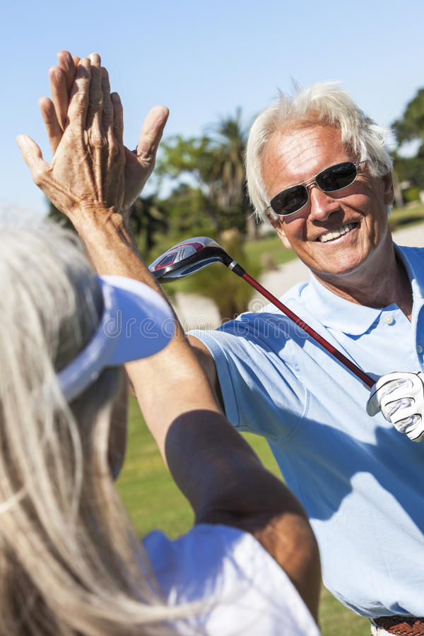 Pares superiores felizes que jogam o golfe fotos de stock