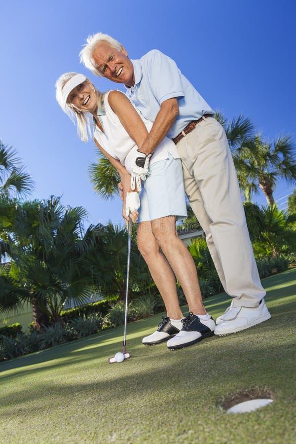 Pares superiores felizes que jogam o golfe que pôr sobre o verde fotos de stock royalty free