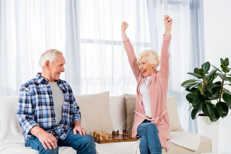 pares superiores felizes que jogam a xadrez em casa fotografia de stock royalty free