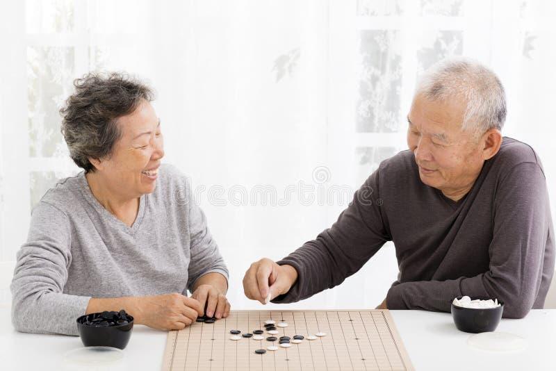 Pares superiores felizes que jogam a xadrez na sala de visitas fotografia de stock