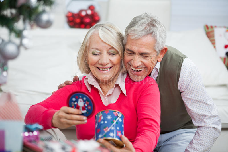 Pares superiores felizes que olham o presente do Natal imagens de stock royalty free