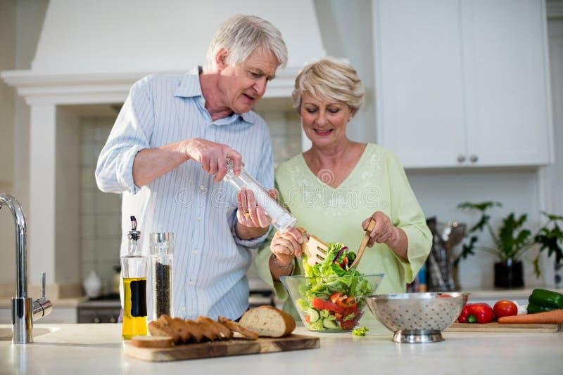 Pares superiores felizes que preparam a salada vegetal foto de stock