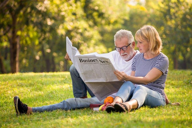 Pares superiores felizes que relaxam no jornal da leitura do parque junto pessoas adultas que sentam-se na grama no parque do ver imagem de stock royalty free