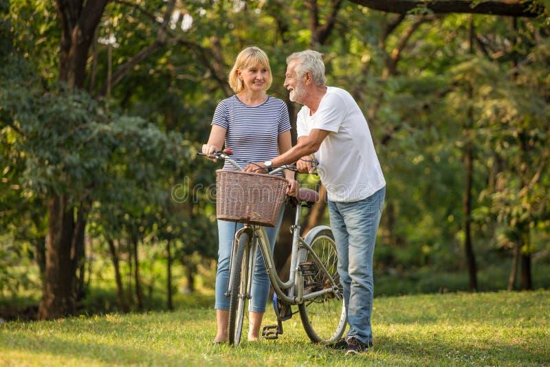 Pares superiores felizes que relaxam no parque que anda com bicicleta e que fala junto no tempo de manhã pessoas adultas no parqu imagem de stock