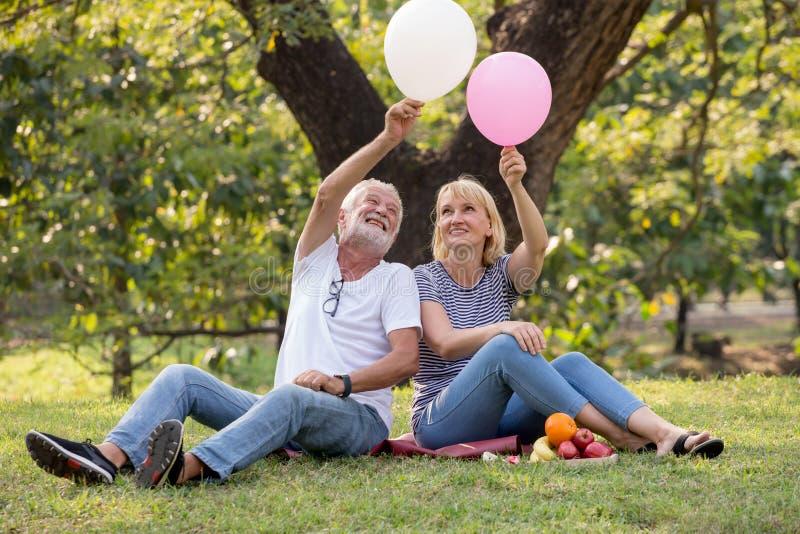 Pares superiores felizes que relaxam no parque que joga balões junto pessoas adultas que sentam-se na grama no parque do verão De fotografia de stock