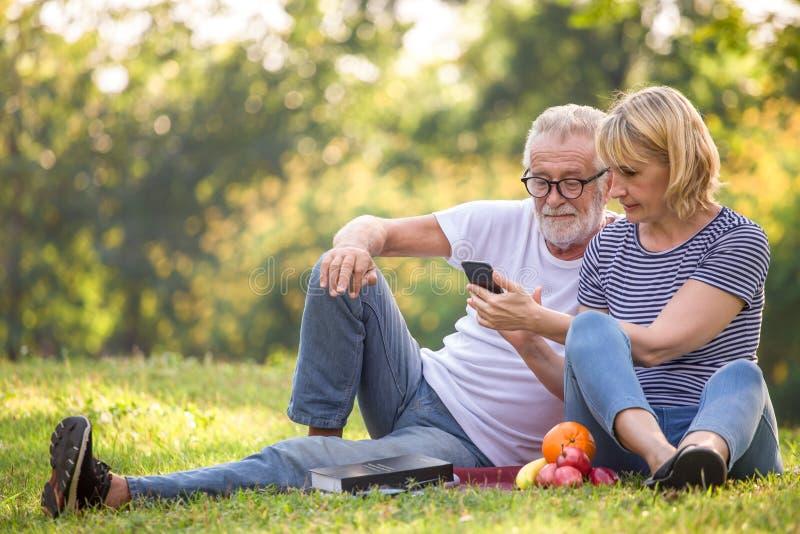 Pares superiores felizes que relaxam no parque usando o smartphone junto pessoas adultas que sentam-se na grama no parque do verã imagem de stock