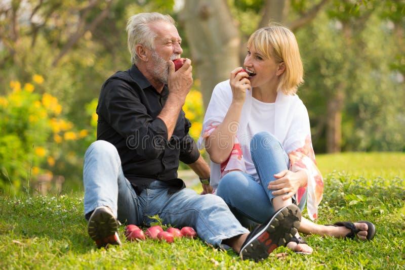 Pares superiores felizes que relaxam no tempo de manhã da maçã comer do parque junto pessoas adultas que sentam-se na grama no pa imagem de stock