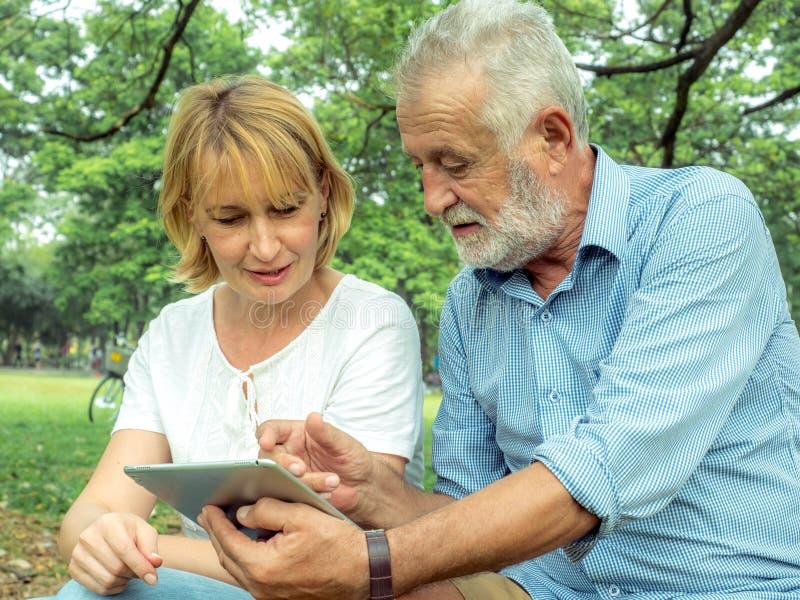 Pares superiores felizes que sentam-se na grama verde e que apreciam usando o portátil para o entretenimento em linha no parque,  fotos de stock