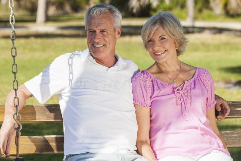 Pares superiores felizes que sentam-se no banco na luz do sol foto de stock