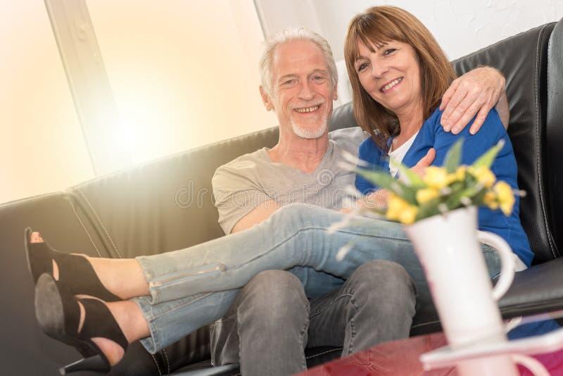 Pares superiores felizes que sentam-se no sofá e que abraçam-se, efeito da luz foto de stock royalty free