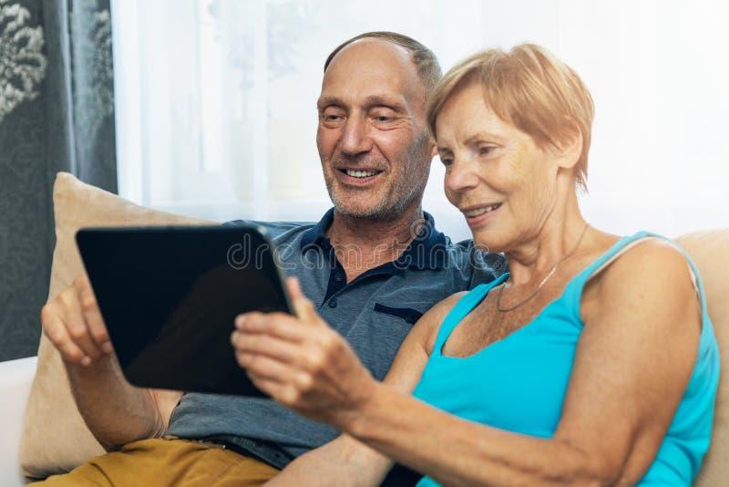 Pares superiores felizes que sentam-se no sofá e que usam a tabuleta digital imagem de stock