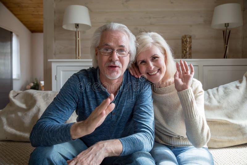 Pares superiores felizes que têm a chamada video que fala da casa imagens de stock royalty free