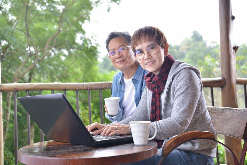 Pares superiores felizes usando o laptop em casa foto de stock royalty free