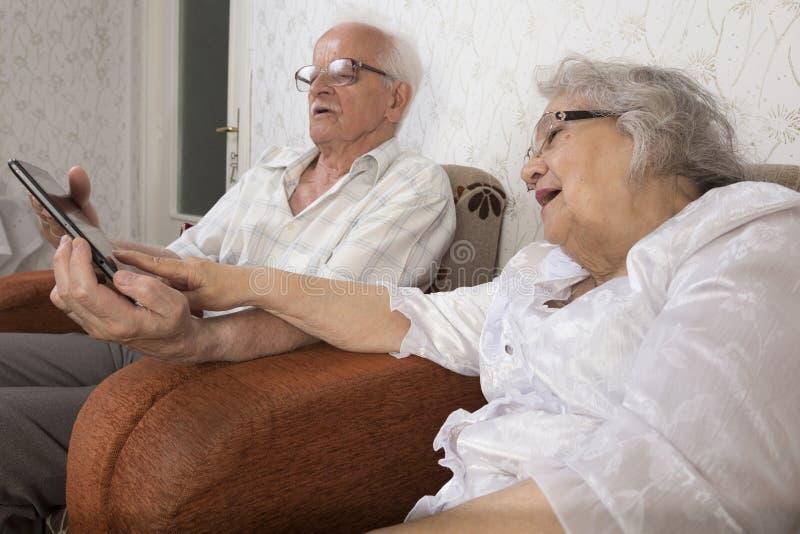 Pares superiores felizes usando o tablete moderno foto de stock