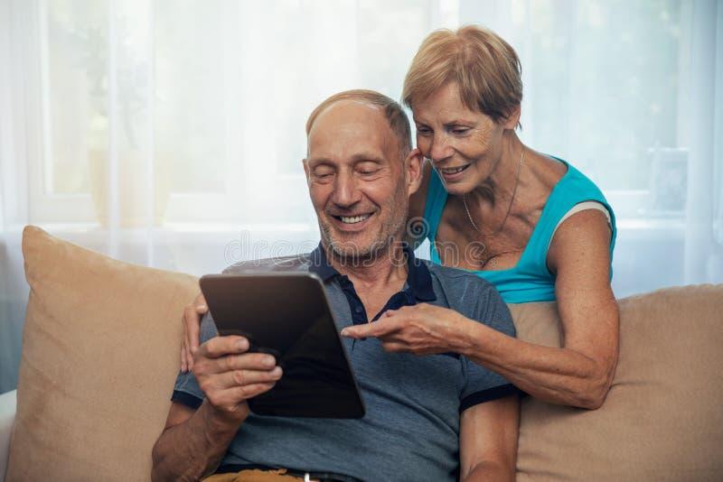 Pares superiores felizes usando a tabuleta digital em casa foto de stock royalty free