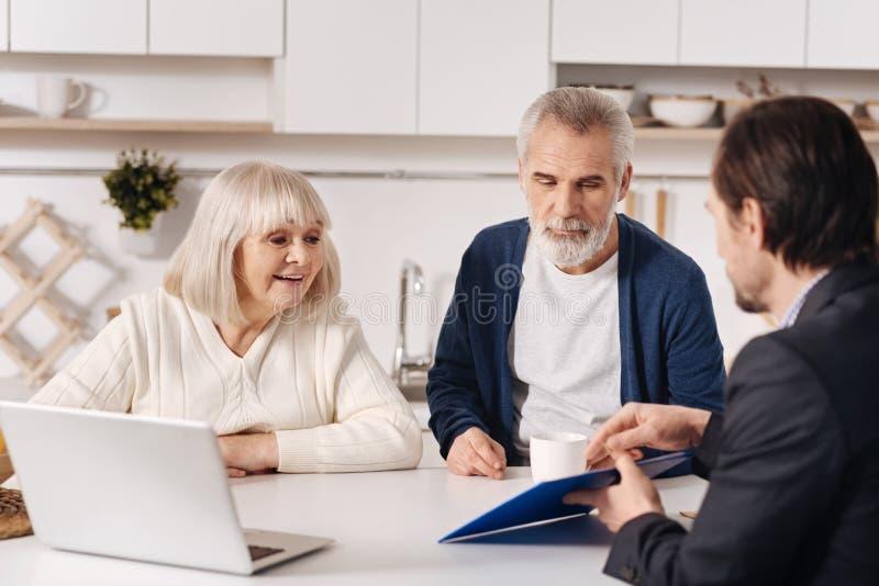 Pares superiores involvidos que têm a conversação com corretor de imóveis em casa foto de stock royalty free