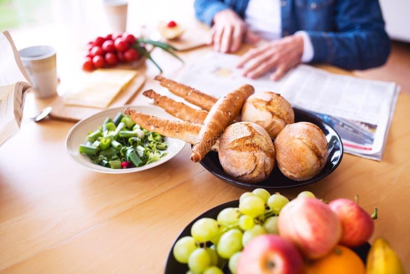 Pares superiores irreconhecíveis que comem o café da manhã em casa fotografia de stock
