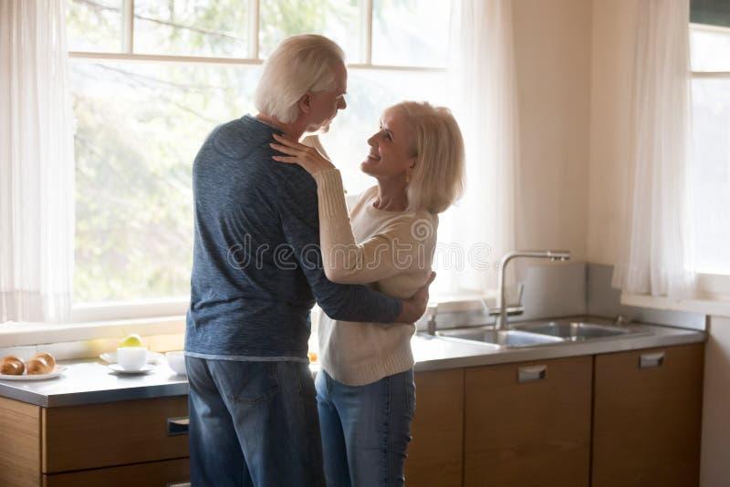 Pares superiores loving felizes que abraçam e que dançam na cozinha imagem de stock royalty free
