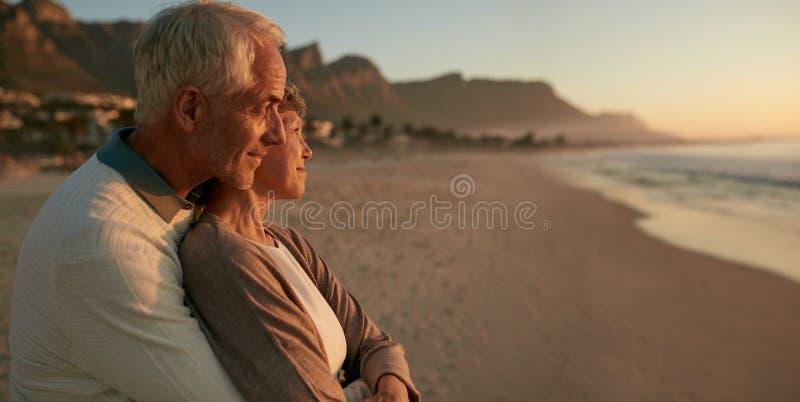 Pares superiores loving que apreciam o por do sol na praia fotografia de stock