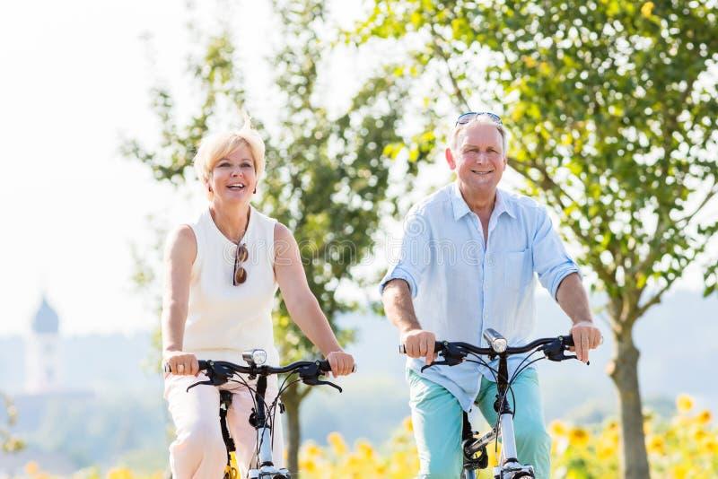 Pares superiores, mulher e homem, montando suas bicicletas imagens de stock