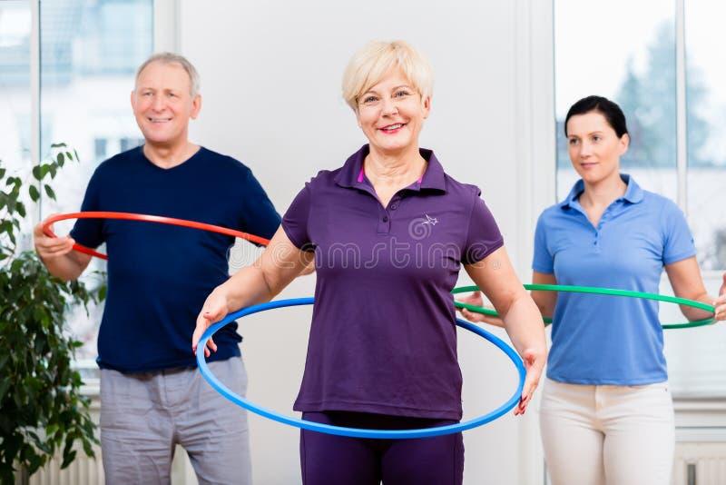Pares superiores na fisioterapia que faz o exercício com aro do hula fotos de stock royalty free