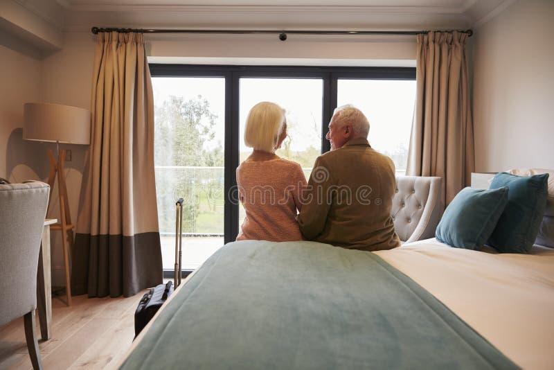 Pares superiores nas férias que sentam-se na cama do hotel imagem de stock royalty free