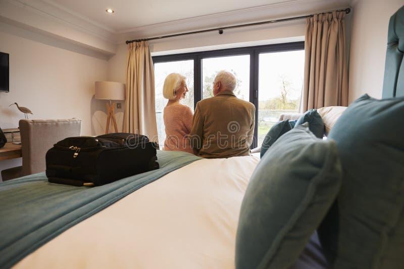 Pares superiores nas férias que sentam-se na cama do hotel fotografia de stock