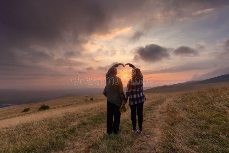 Pares superiores no amor na montanha no por do sol idílico imagens de stock royalty free