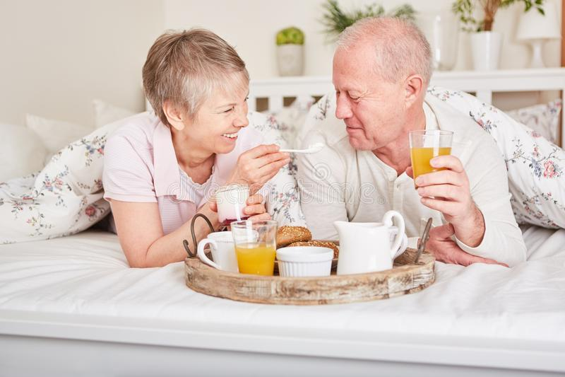 Pares superiores no amor que come o café da manhã fotos de stock royalty free