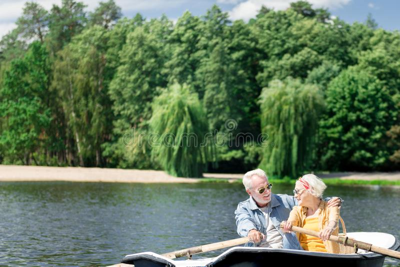 Pares superiores que abraçam ao apreciar a natureza e o esporte de barco imagem de stock royalty free