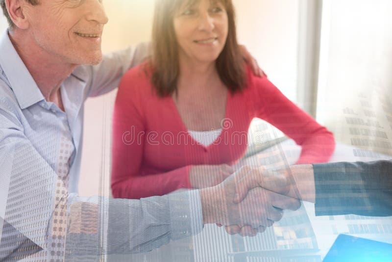 Pares superiores que agitam as mãos com corretor de imóveis; exposição múltipla imagens de stock royalty free