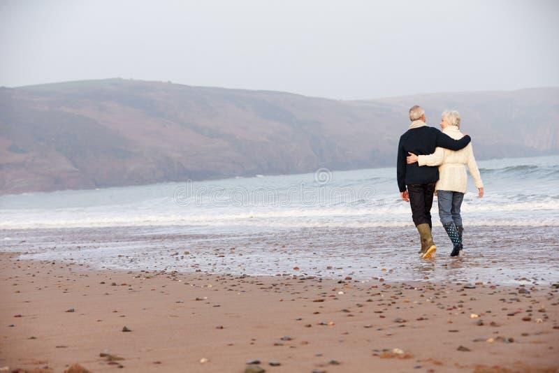 Pares superiores que andam ao longo da praia do inverno foto de stock royalty free