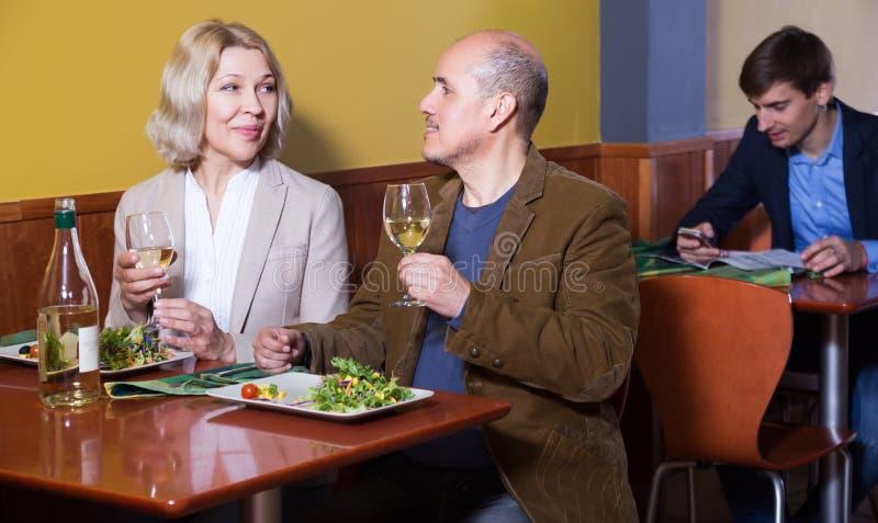Pares superiores que apreciam o alimento no restaurante imagens de stock