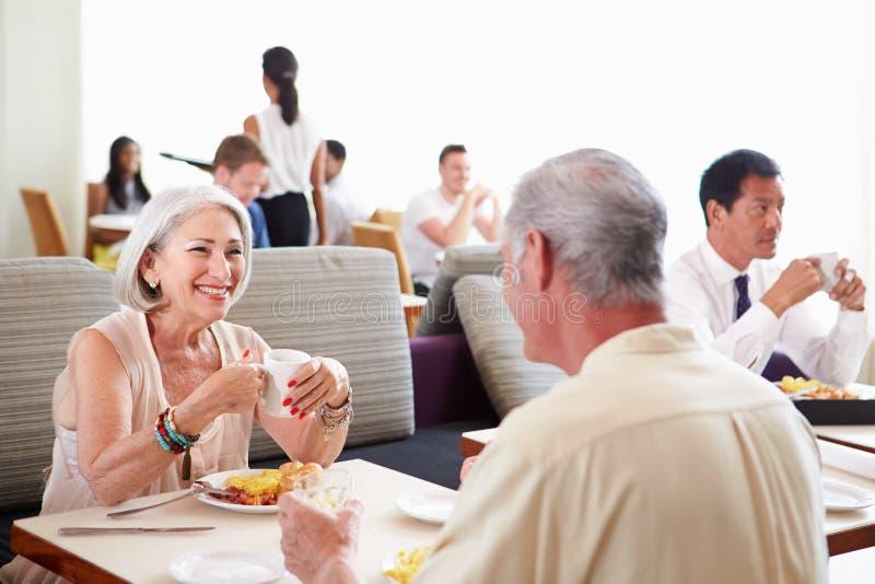 Pares superiores que apreciam o café da manhã no restaurante do hotel imagem de stock