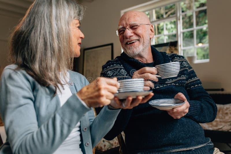 Pares superiores que apreciam o café em casa foto de stock royalty free