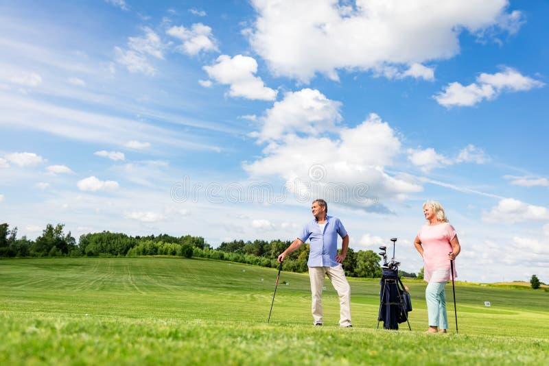 Pares superiores que apreciam o jogo de golfe foto de stock royalty free