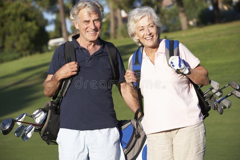 Pares superiores que apreciam o jogo do golfe fotografia de stock