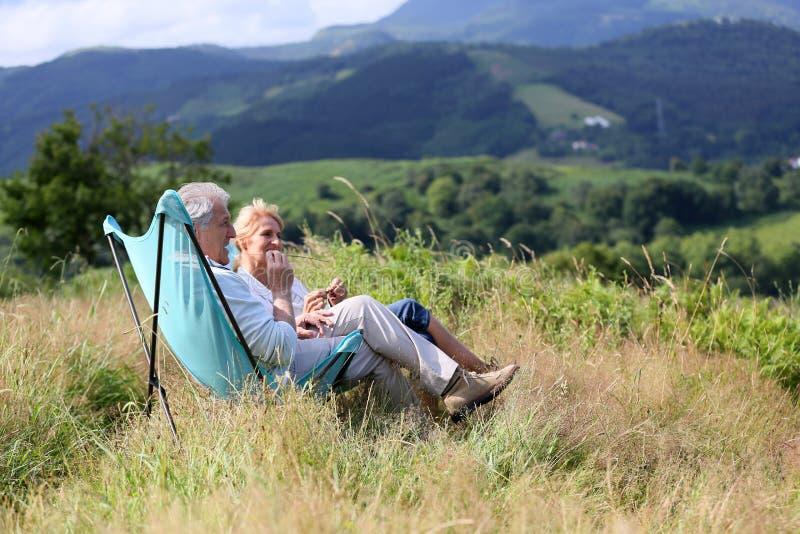 Pares superiores que apreciam a paisagem bonita das montanhas fotos de stock royalty free