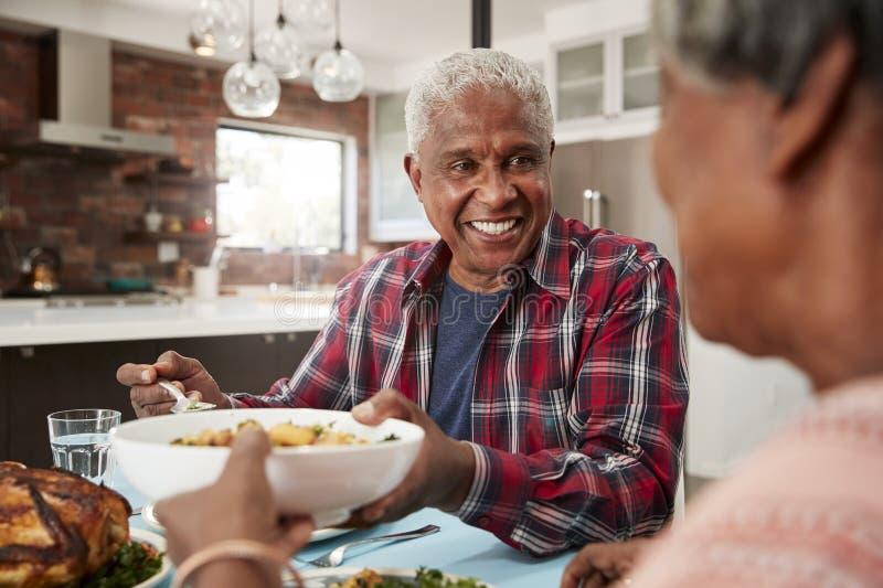 Pares superiores que apreciam a refeição em torno da tabela em casa foto de stock royalty free