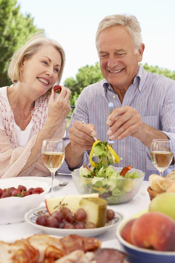 Pares superiores que apreciam a refeição exterior junto foto de stock