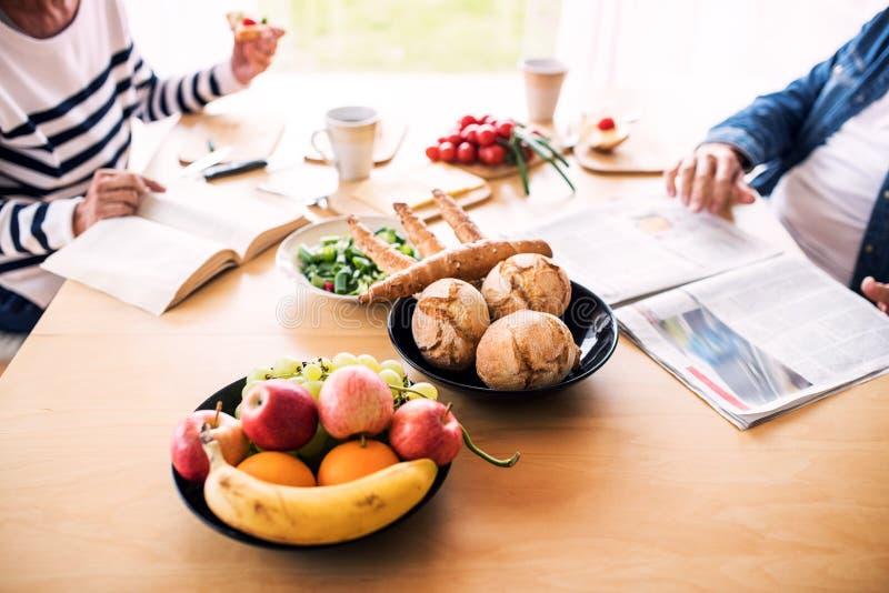 Pares superiores que comem o café da manhã em casa imagem de stock royalty free